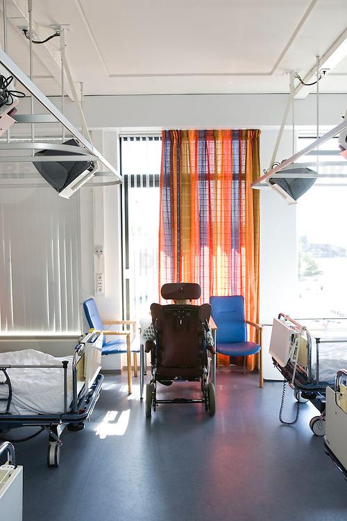 Nederland Rotterdam  31-08-2009 20090831 Foto: David Rozing .Serie over zorgsector, Ikazia Ziekenhuis Rotterdam. Afdeling neurologie, stroke unit,een oude man die een hersenbloeding, beroerte heeft gehad zit in een rolstoel bij het raam alleen op zaal.  An old patient who suffered a stroke, in a wheelchair sitting alone in dorm room hospital room. .Na een ernstige beroerte wordt u opgenomen in een gespecialiseerde afdeling of een afdeling intensieve zorgen van het ziekenhuis. Na de eerste 24 uur is het nodig om een aangepast revalidatieprogramma te starten.    .Foto: David Rozing ..Holland, The Netherlands, dutch, Pays Bas, Europe, nursing, aansterken, Holland, The Netherlands, dutch, Pays Bas, Europe, oud, oude, op leeftijd, revalidatie, revalideren, revalidation, lege, leeg, alleen, eenzaam, eenzaamheid, , mobiliteit, niet mobiel zijn, verlamd zijn, niet goed kunnen lopen, ouderen,,copy space, ruimte voor tekst,ziekenhuiszaal,ziektekosten,zorgverlening,oud ,ouderen, bejaard, bejaarde, bejaarden, op leeftijd zijn, oude van dagen, ouderenzorg, bejaardenzorg, man, achter de geraniums zitten, alleen zijn, eenzaam, eenzaamheid, ouderdom