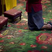 A Taoist worshiper kneels and prays before the idols.