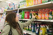 Conscience shopper comparing prices and ingredients in a supermarket detergent aisle. Model Release Available