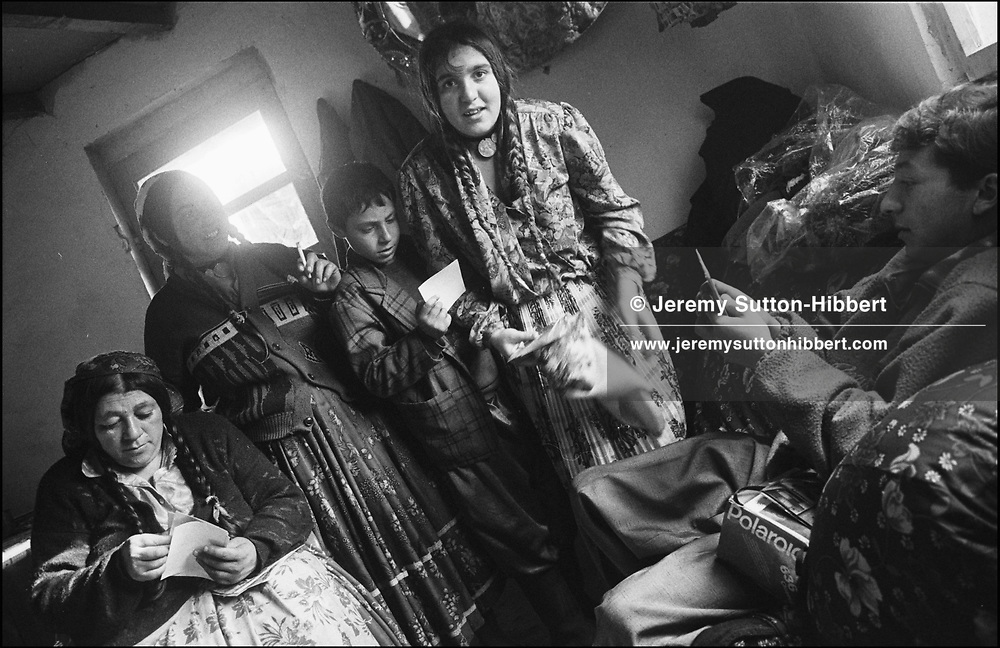 BULACHE MIHAI, ON RIGHT, AND HIS FAMILY LOOK AT PHOTOS OF THEMSELVES TAKEN BY ME ON A PREVIOUS VISIT. SINTESTI, ROMANIA, NOVEMBER 1996..©JEREMY SUTTON-HIBBERT 2000..TEL./FAX. +44-141-649-2912..TEL. +44-7831-138817.