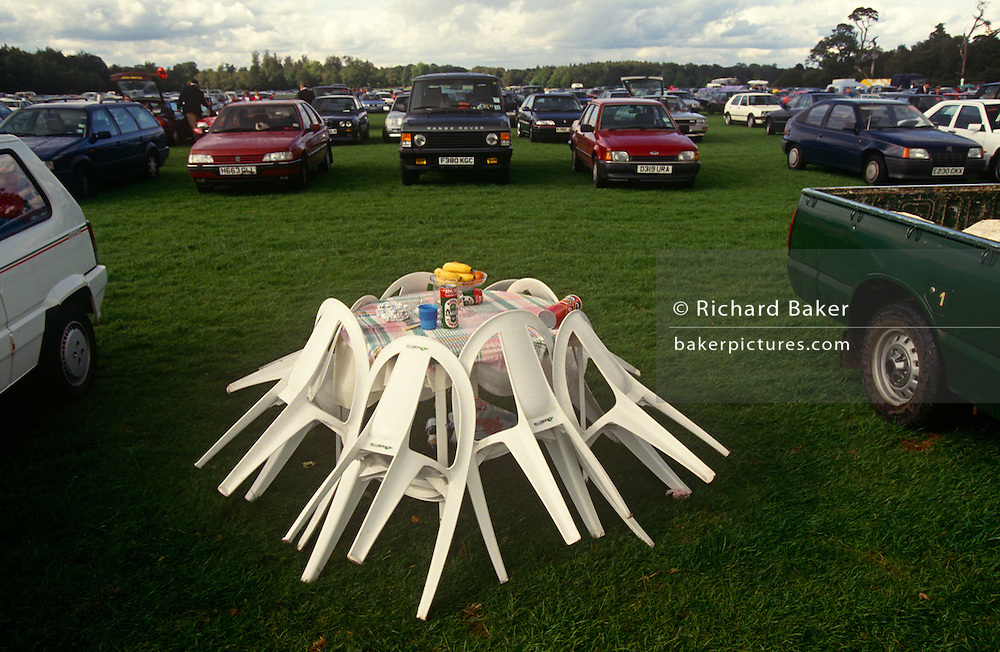 Garden table and chairs are tidily propped up awaiting its owners to return to the grassy car park from the races during Ladies Day at Royal Ascot racing week. Cans of lager, a fruit bowl and some Pringles hint at the snacks already eaten. Royal Ascot is held every June and is one of the main dates on the sporting calendar and social season. Over 300,000 people make the annual visit to Berkshire during Royal Ascot week, making this Europe's best-attended race meeting. There are sixteen group races on offer, with at least one Group One event on each of the five days. The Gold Cup is on Ladies' Day on the Thursday. There is over £3 million of prize money on offer.