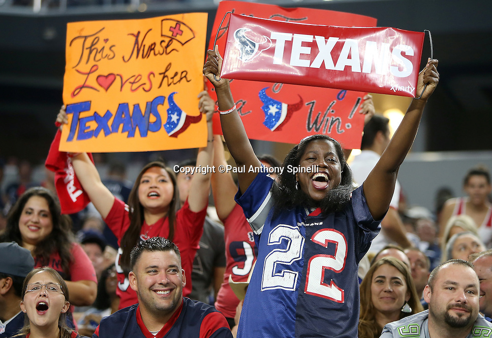 Houston Texans fans hold up signs supporting the team as they cheer after the Texans score a fourth quarter touchdown that ties the score at 14-14 during the 2015 NFL preseason football game against the Dallas Cowboys on Thursday, Sept. 3, 2015 in Arlington, Texas. The Cowboys won the game 21-14. (©Paul Anthony Spinelli)
