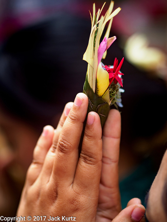 "02 AUGUST 2017 - UBUD, BALI, INDONESIA: A woman holds a small floral offering during the ""Merchants' Day"" ceremony at the Pura (Temple) Melanting Pasar Ubud, the small Hindu temple in the Ubud market. It's a day that merchants throughout Ubud come to the temple to make offerings and pray for prosperity.    PHOTO BY JACK KURTZ"