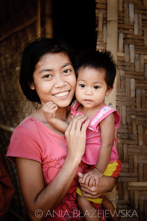 Indonesia, Lombok. Mother with a baby in her arms standing in the front of her bamboo house in Kuta.