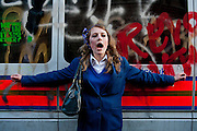 A school girl attempts to protect a vandalised police van in Whitehall during student protests over fees.