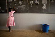 A girl solves a math problem on the black board during class at the Essaout primary school in the village of Essaout, Senegal, on Thursday June 14, 2007...