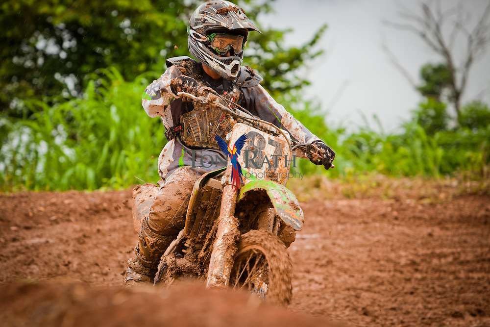 Motorcycle rider splattered with mud on an extremely muddy outdoor motocross race track in Belmopan Belize.