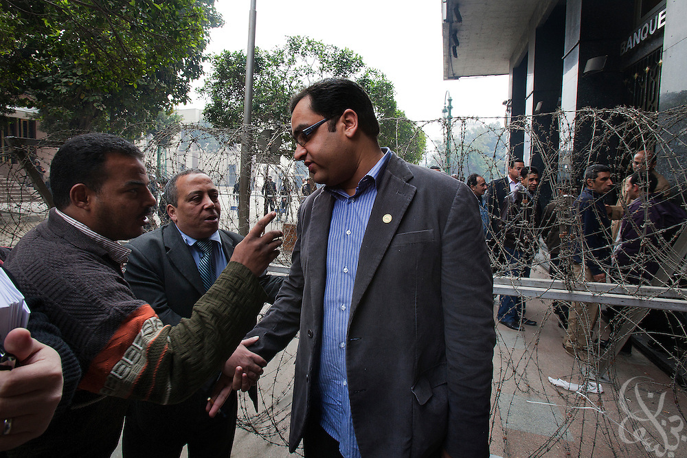 Egyptian Parliamentarian-elect Zyad Elelaimy speaks with supporters before passing through a barbed wire security checkpoint  on his way to the historic first session of Egypt's newly elected Parliament session Jan 23, 2012 in Cairo, Egypt.