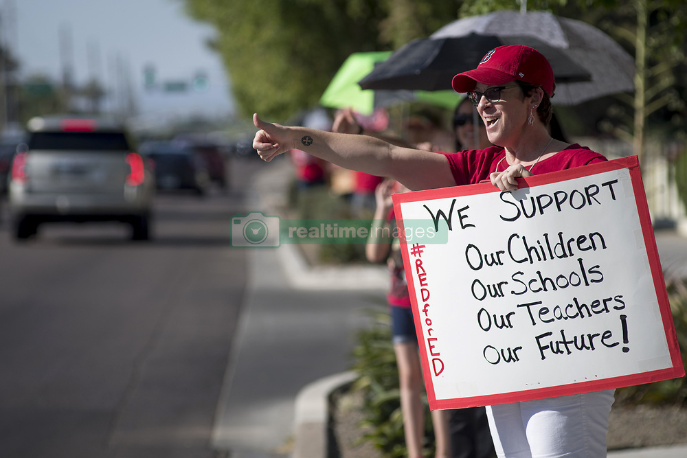 April 25, 2018 - Scottsdale, Arizona, U.S - Scottsdale, Arizona, classified employee Julie Gildersleeve  reacts to motorists honking in support and colleagues demonstrate for improved funding for all Arizona schools.  Teachers are planning a walk-out statewide on Thursday, April 26 if Governor Doug Ducey and the Legislature fail to make changes to the next state budget to overcome at least ten years of budget shortcomings for teachers, equipment and facilities. Arizona is ranked 49th in the nations for benchmark statistics in measuring the quality of schools. (Credit Image: ©  via ZUMA Wire)