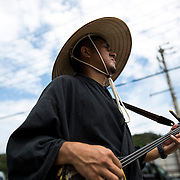 OKINAWA, JAPAN - AUGUST 17 : Shamisen player sing and chant while Eisa folk dancers perform a modern dance in a small village in Nago during the Obon festival to honour the spirits of their ancestors on August 17, 2016, Okinawa prefecture, Japan.  (Photo by Richard Atrero de Guzman/NURPhoto)