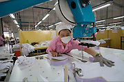 A factory worker cuts material to be used to sew bras in the Top Form factory in Longnan, China.