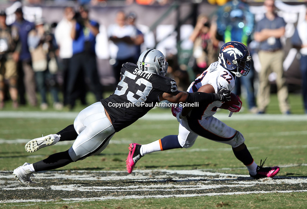 Denver Broncos running back C.J. Anderson (22) tries to elude a tackle attempt by Oakland Raiders outside linebacker Malcolm Smith (53) after catching a first down pass on third down with 11 yards to go in the fourth quarter during the 2015 NFL week 5 regular season football game against the Oakland Raiders on Sunday, Oct. 11, 2015 in Oakland, Calif. The Broncos won the game 16-10. (©Paul Anthony Spinelli)