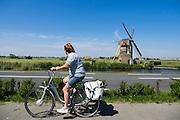 Bij Oegstgeest rijdt een vrouw op een fiets langs een windmolen.<br /> <br /> Near Oegstgeest a woman cycles on a city bike near a wind mill