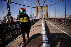 March 18, 2020, New York, New York, USA: A person wearing a mask due to Coronavirus fears, crosses an empty Brooklyn Bridge. Coronavirus fears spread as people wear masks and subway stations and various other venues empty out. (Credit Image: © Starmax/Newscom via ZUMA Press)
