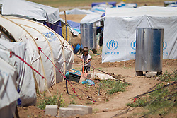 © Licensed to London News Pictures. 12/05/2013. Dohuk, Iraq. A young Syrian refugee plays with a shovel outside his tent at the Domiz refugee camp in Iraqi-Kurdistan, set up for those escaping the ongoing civil war in Syria. The camp, close to the city of Dohuk, now houses in the region of 45,000 refugees, with around 400 new arrivals every day. Photo credit: Matt Cetti-Roberts/LNP