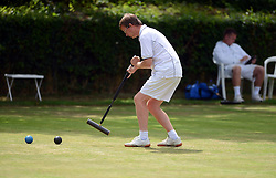 © Licensed to London News Pictures. 14/08/2013. Surbiton, UK. Ian Lines, England plays while his opponent David Maugham, England relaxes.People participate in the14th World Association Croquet Championship at the Surbiton Croquet Club, Kingston upon Thames on the 14th August 2013. The Final will be played on Sunday 18th August. 80 competitors from 20 countries are taking part. Photo credit : Mike King/LNP