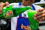 06 APRIL 2013 - SANPATONG, CHIANG MAI, THAILAND:  Green Fanta for sale at the market in Sanpatong, Chiang Mai province, Thailand. The buffalo market in Sanpatong (also spelled San Patong) started as a weekly gathering of farmers and traders buying and selling water buffalo, the iconic beast of burden in Southeast Asia, more than 60 years ago and has grown into one of the largest weekend markets in northern Thailand. Buffalo and cattle are still a main focus of the market, but traders also buy and sell fighting cocks, food, clothes, home brew and patent medicines.           PHOTO BY JACK KURTZ