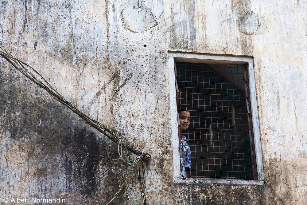 Young boy in window of old building, Yangon