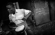 NAIROBI, KENYA - MARCH 17, 2010: A Kenyan youth plays a drum on the streets of Kibera slum. Nearby, graffiti painted the famous Kenyan artist Solo7 is a reminder of the recent post-election violence. <br />