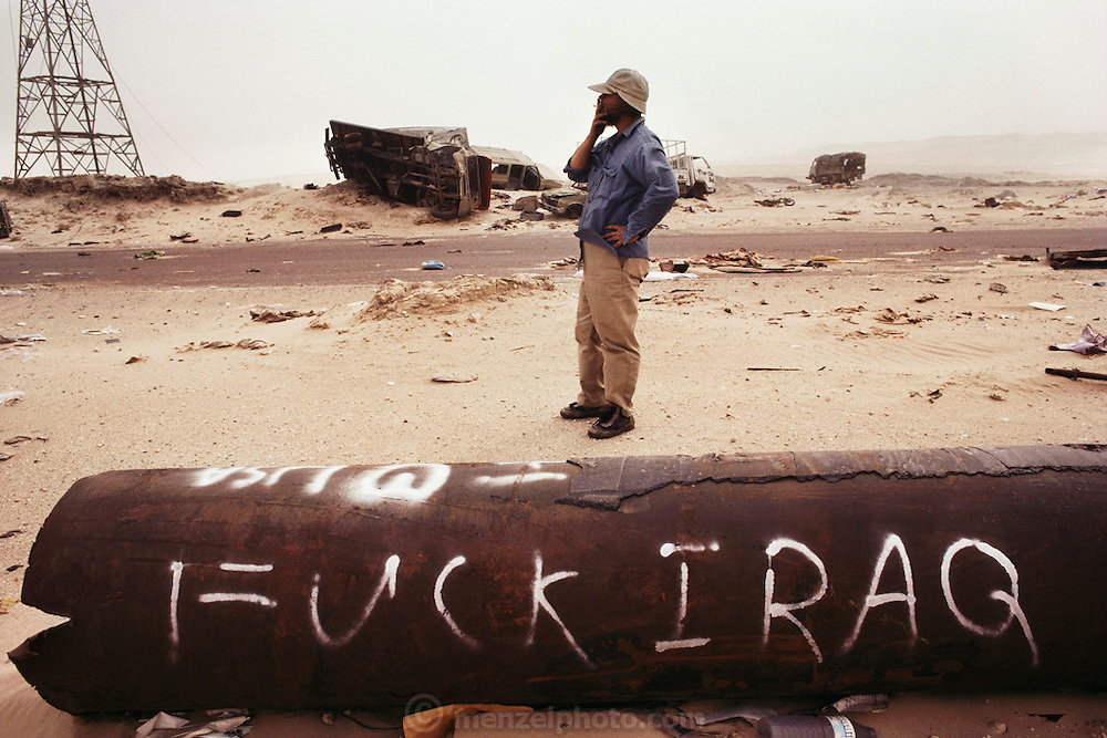 "Author Tim Cahill having a cigarette break while viewing the vehicular carnage still remaining on the Jahra Road in July 1991, from Kuwait City to Basra, Iraq. American forces chased and trapped retreating Iraqi forces north of Kuwait City on the night of February 25 and the day of February 26, 1991. These units withdrew via the Jahra road on the way to Basra, an escape route that has become known as the ""highway to hell."" They were attacked by coalition aircraft and it is estimated that several thousand retreating Iraqis died.."