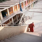 A Tibetan monk walks down a flight of stairs at a monestery in Dharamsala, India, in 11/91.