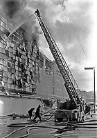Firemen fight blaze at Belfast Co-op's main store in York Street, following the explosion of a Provisional IRA bomb. Several people were slightly injured. At the time it was stated that £8M worth of damage was caused and that around 1000 jobs were endangered. NI Troubles. Ref: 19720510003<br />