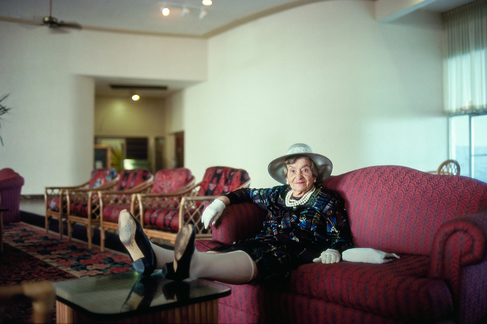 Elderly woman in a hat, gloves, and pearls sitting on a couch in a Miami Beach hotel lobby with her feet up on a coffee table