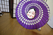 happy smiling Japanese Okame mask on a modern antique style umbrella