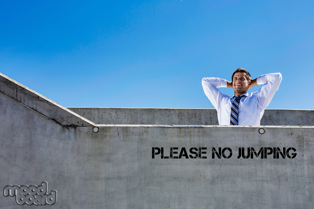 Portrait of mature businessman relaxing on rooftop