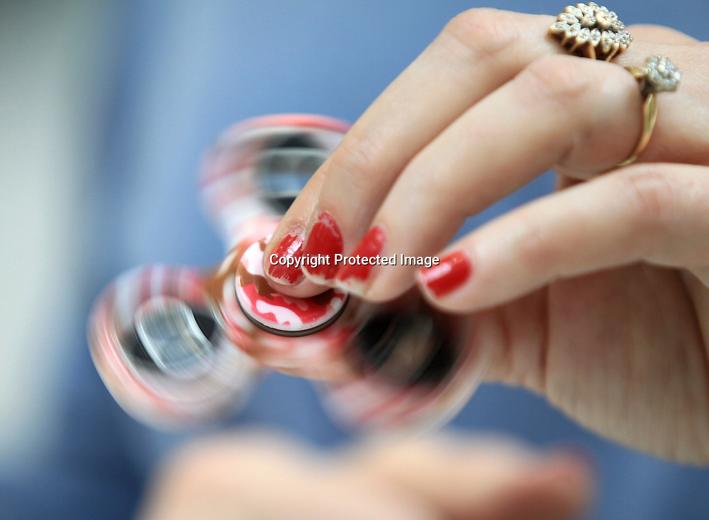 Martha Mitchell, right, an employee with Sunny Shades, spins a Fidget Spinners as she shows a customer what the craze is all about at the Fidget Spinner kiosk inside the Mall at Barnes Corssing