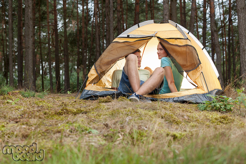 Young couple camping in forest