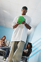 Young man at bowling alley holding ball portrait low angle view