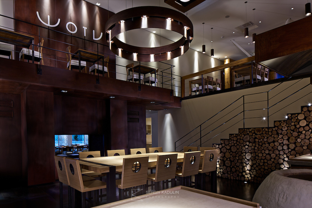 Interior design of georgian restaurant Shoti in Kyiv, Ukraine. Ground floor view, with preparation table and oven in the foreground, and first floor with Shoti logo on the wall in the background.