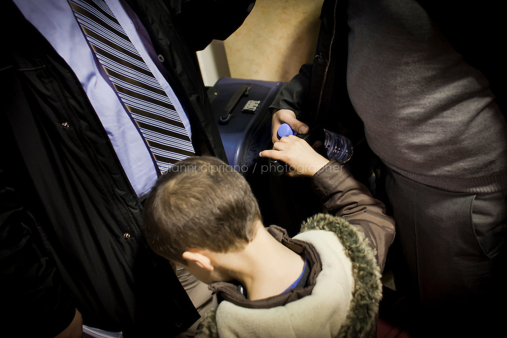 25 February 2011. Valletta, Malta. A tired child between his father (right) and an interviewer (left) at the Maltese Customs after stepping down from the ferry that evacuated them from Libya.  A U.S.-chartered ferry evacuated Americans and other foreigners out of Libya on Friday and brought them to the Mediterranean island of Malta. The Maria Dolores ferry, after three days of delays, brought over 300 passengers, including at 167 U.S. citizens, away from Libya where Colonel Gaddafi's forces continue to clash with anti-government demonstrators.<br /> <br /> <br /> &copy;2011 Gianni Cipriano<br /> cell. +1 646 465 2168 (USA)<br /> cell. +39 328 567 7923<br /> gianni@giannicipriano.com<br /> www.giannicipriano.com