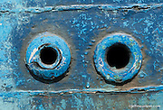 Detail image of a blue holes on the hull of a fishing boat.