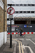A cyclist pedals a Santander rental bike across a street corner featuring traffic direction arrows, 7th March 2018, in London England.
