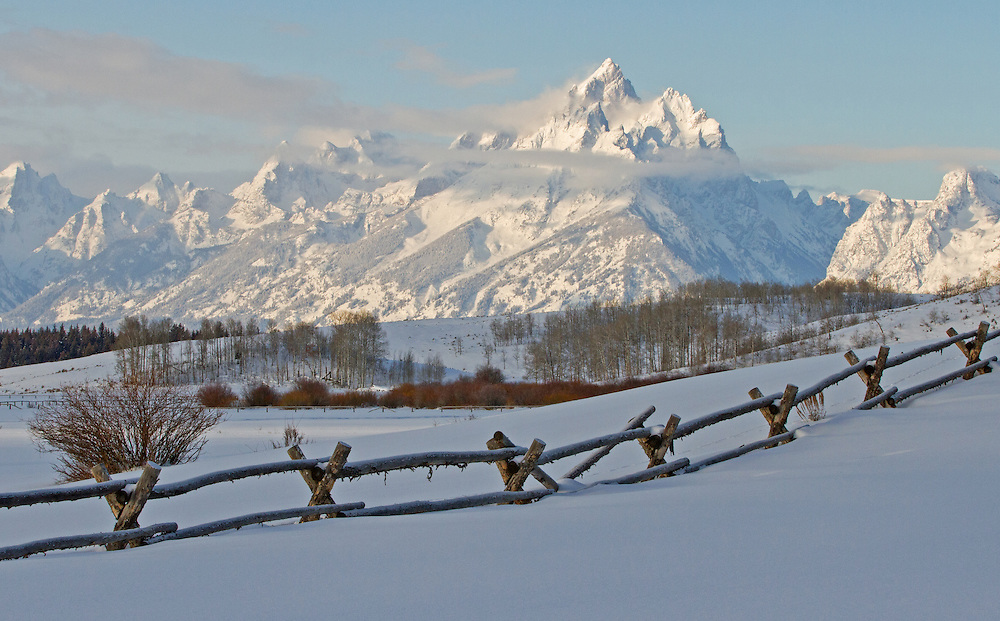 At 13,770 feet above sea level, the Grand Teton and the Cathedral Group rise above lingering pre-dawn cloudcover on a frigid February morning.
