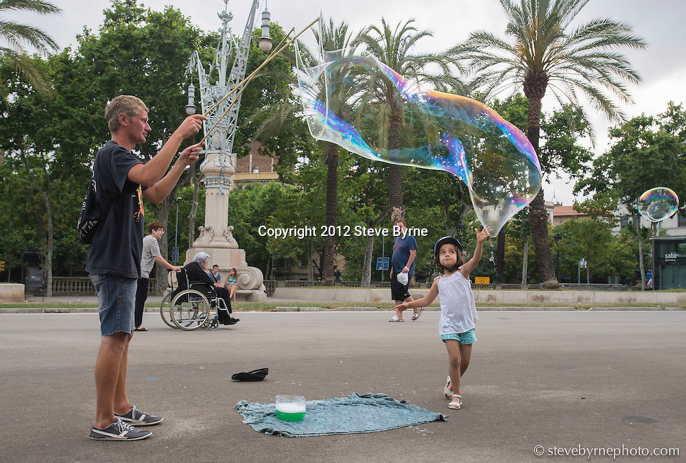 A local entertains children by making bubbles in a park near el Barrio Gotico.