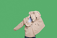 Young man struggling to wear jacket over colored background
