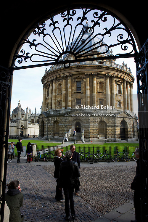 Through Bodleian Library arch, visitors tour Radcliffe Camera 150 feet (46 meters) above cobbled Radcliffe Square, Oxford.