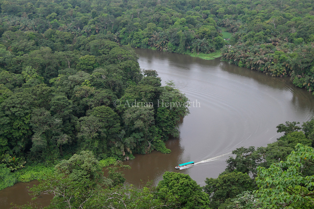 Tourist boat on natural rainforest canal seen from Tortuguero Hill (Cerro Tortuguero). Barro Colorado Wildlife Refuge. Costa Rica. <br />