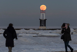 © Licensed to London News Pictures. 01/01/2018. CHICAGO, USA. Passers by walk across the ice covered North Avenue beach as the supermoon rises on one of the coldest New Year's Days in decades. A snowy owl can also be seen atop the beacon on the jetty.  The moon is at its closest point, the perigee, to Earth during its monthly orbit and appears 30% brighter and 14% larger.  January 2018 sees a supermoon known as a 'wolf moon' on 1 January and a 'blue moon' on 31 January.  Photo credit: Stephen Chung/LNP