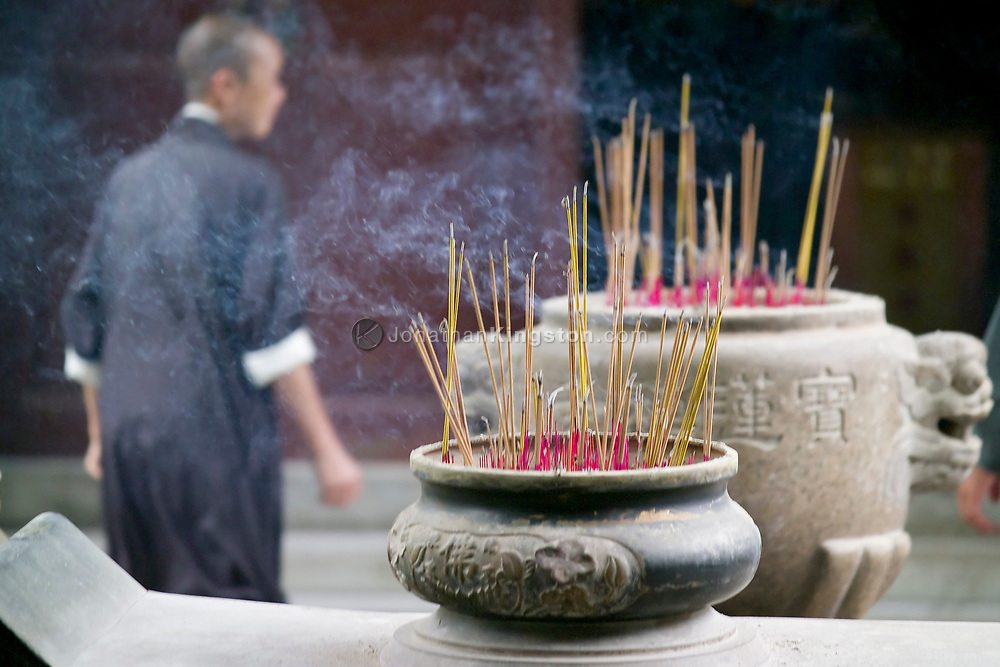 A monk walks past burning incense sticks at the Po Lin Monastery, Lantau Island, Hong Kong, China.  The Po Lin Monastery is a major tourist attraction due to the Tian Tan Buddha, the worlds tallest outdoor seated bronze Buddha.  Hong Kong Special Administrative Region is one of two special administrative regions of the People's Republic of China.