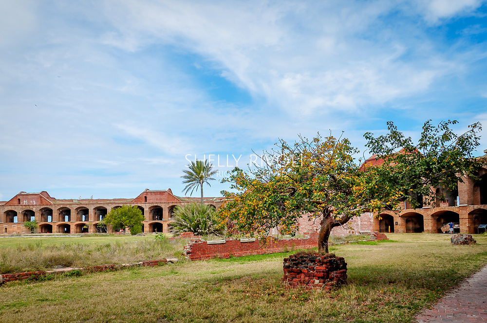 Courtyard of Fort Jefferson with trees and green grass, brick walls with arches surround at Dry Tortugas National Park, Florida.