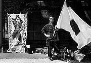 "A nationalist man holds the Japanese flag next to a poster reading ""The spirit of the samurai that changed the world/Don't forget the Greater Asia War!"" outside Yasukuni Shrine in Tokyo, Japan Every year on August 15, the day Japan officially surrendered WWII, tens of thousands of Japanese visit the controversial shrine to pay their respects to the 2.46 million war dead enshrined there, the majority of who are soldiers and others killed in WWII but also includes 14 Class A convicted war criminals, such as Japan's war-time prime minister Hideki Tojo. Each year speculation escalates as to whether the country's political leaders will visit the shrine, the last to do so being Junichiro Koizumi in 2005. Nationalism in Japan is reportedly on the rise, while sentiment against the nation by countries that suffered from Japan's wartime brutality, such as China, has been further aggravated by Japan's insistence on glossing over its wartime atrocities in school text books..Photographer:Robert Gilhooly.."