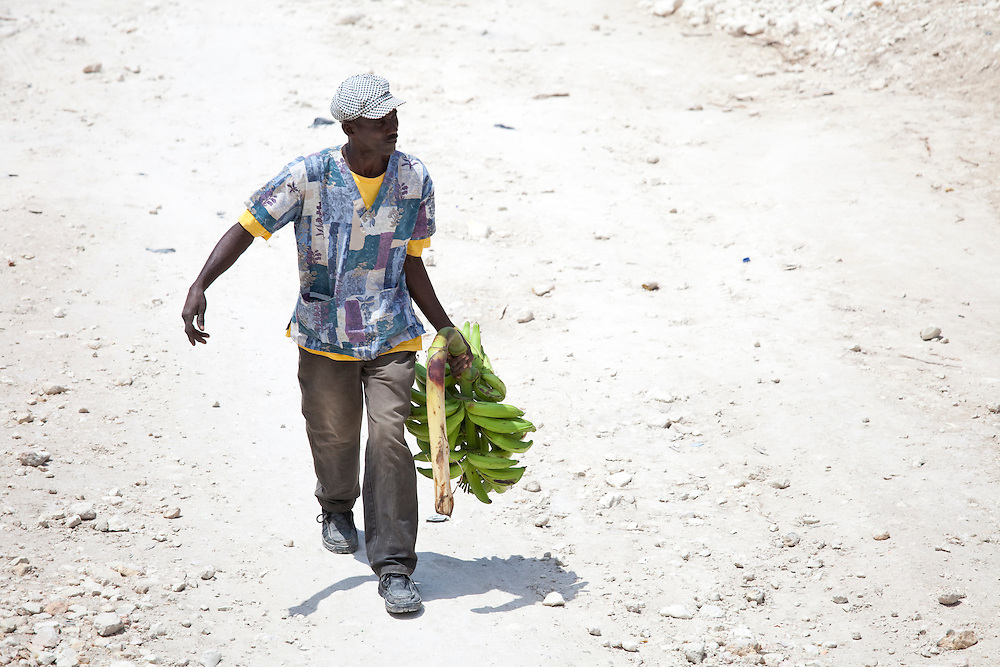 A man carries a bunch of plntains down a dusty road in Anse a Galet in Ile de La Gonave, Haiti