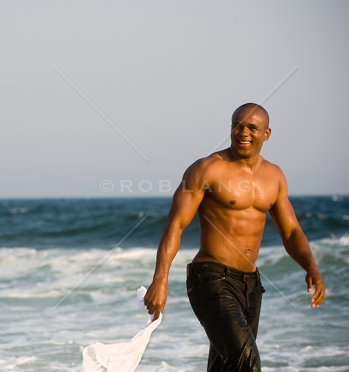 Shirtless young african american man walking beside the ocean in wet clothes
