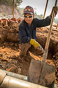 15 MARCH 2013 -  OUDOMXAY, LAOS: A construction worker on the site of a new gas station being built on Highway 13 between Oudomxay and Luang Prabang, Laos.  PHOTO BY JACK KURTZ