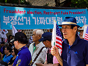 16 JUNE 2018 - SEOUL, SOUTH KOREA: South Korean protesters stand in front of a banner alleging election fraud during the election of South Korean President Moon Jae-in during a protest against President Moon. Most of the protesters support jailed former President Park Geun-hye. President Moon Jae-in was elected in 2017 after Park was impeached, tried and convicted on corruption charges. The protesters allege that Moon is too soft on North Korea and can't be trusted to negotiate with North Korean leader Kim Jong-un. They support US President Donald Trump's efforts to negotiate with the North Korean strongman.  PHOTO BY JACK KURTZ