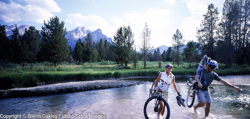 A couple carries their mountain bikes across a creek, Sawtooth Mtns, Idaho.